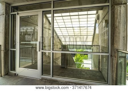 Glass Door And Wall With View Of Slanted Frosted Roof Over Stairway Of Building
