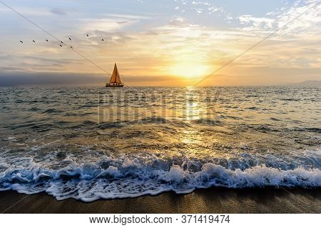 A Sailboat Is Sailing Along The Ocean As Birds Fly In The Sunset Sky