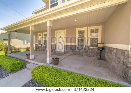 Landscaped Yard And Pathway In Front Of Porch And White Front Door Of Home
