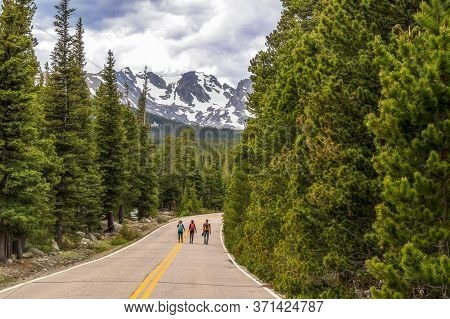 Unrecognizable Tourists Walking On The Road To Brainard Lake And Indian Peaks Near Nederland, Colora
