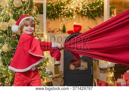 Dreamy Toddler On Christmas Eve. For Christmas And New Year Posters. Santa Helper Holding A Red Bag