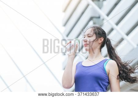 Women Drinking Water Bottle Running Exercise In Modern City Wear Wellness Sportswear Outside. Young