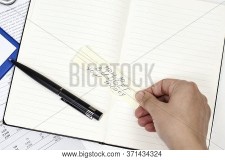 Man Holding Piece Of Paper With Text - How To Budget Your Money. Money Saving, Frugal Living Concept