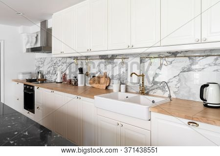 Modern Classic Kitchen Interior With Kitchen Appliances And White Ceramic Sink With Gold Mirror Fauc