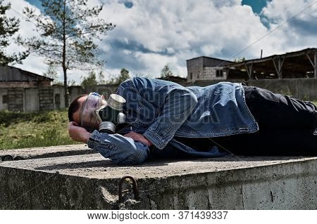 Photo Of The Ruins Of A Building. A Man In A Protective Mask Lies On The Ruins In Sunny Weather.