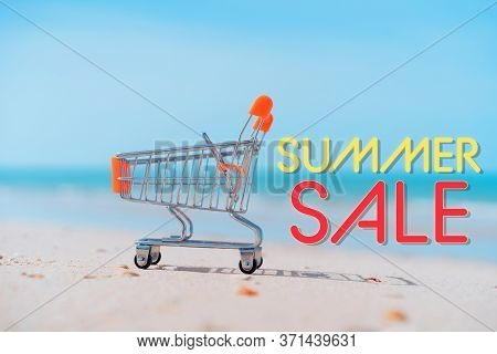 Summer Sale Words On Shopping Basket Cart On Sand Beach With Blue Sky Background. Summer Sale And Bu