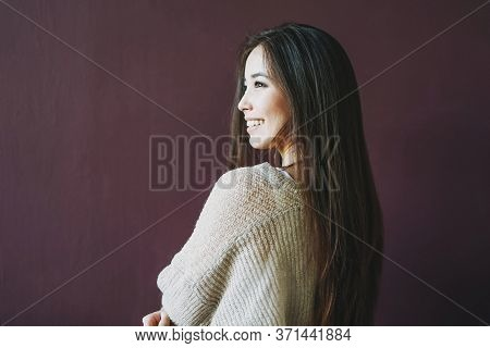Charming Smiling Asian Girl With Long Brown Hair In Beige Sweater Isolated On The Dark Bordo Backgro