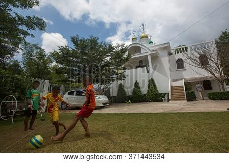 KOH CHANG, THAILAND - MAR 3, 2018: Thai children play in ball near the Russian Orthodox Church. There are currently 10 Orthodox parishes in Thailand, Orthodoxy is practiced by 0.002% of population.