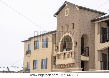 Apartment With Snowy Front Gable Roof And Balustrade On The Arched Balcony