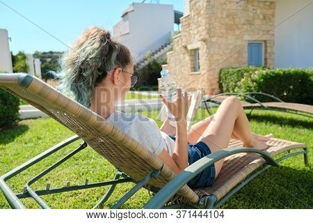 Teenager Girl Relaxing Outdoor Sitting In Rattan Chair On Green Lawn, Reading Book And Drinking Wate