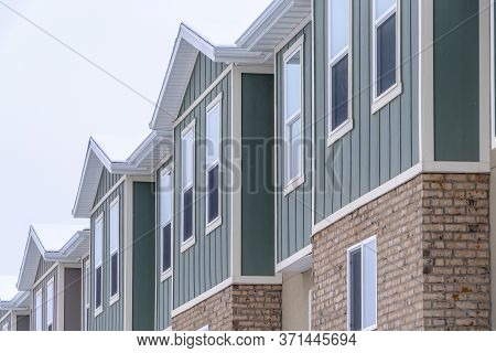Vertical Siding And Stone Brick Wall At The Townhomes Upper Storey Against Sky