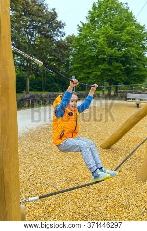 Selective Focus. The Boy Climbing And Sliding On Slide In The Playground. Happy Children Playing And