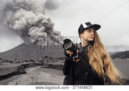 Girl Travel Photographer Stands With Camera Against The Backdrop Of An Erupting Volcano. High Qualit