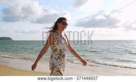 Cheerful Long Haired Girl In Short Summer Sundress Walks Along Empty Beach Near Azure Ocean Water On