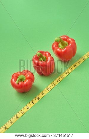 Creative healthy composition from freshly picked ripe red paprika pepper and diagonal yellow measuring tape on a green background, copy space. Low calorie food for reduction of weight.