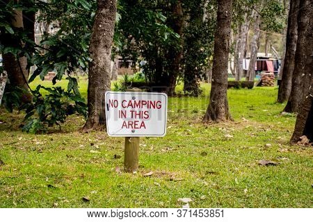 No Camping In This Area Sign On A Green Grass Surrounded By Trees.