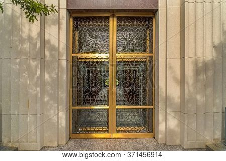 Decorative Wrought Iron Door With Gold Frames In Front Of Glass Door Of Building