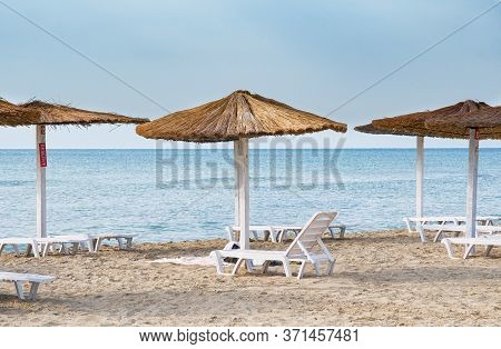 Area Reserved Beach Lounger Chairs And A Umbrella.