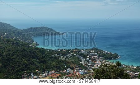 Marvelous Hilly Landscape With Green Forests And Small Building Silhouettes Near Blue Endless Ocean
