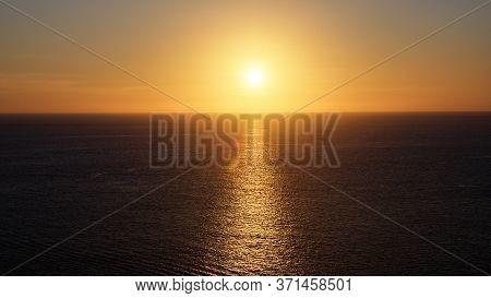 Marvelous Bright Yellow Sunlight Reflected In Calm Endless Ocean Creating Sun Path Under Clear Sky W