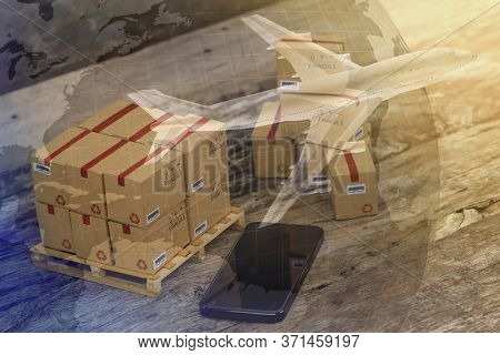 Packing Boxes Small Goods And Cell Phone With A Plane Flies Above World Map. Business Concept About
