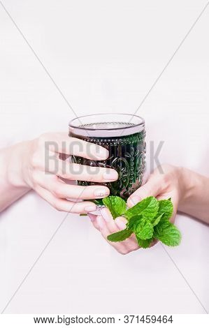 Female Hand Holding Glass Of Green Chlorophyll Drink With Mint Leaves On A Light Pink Background. Co