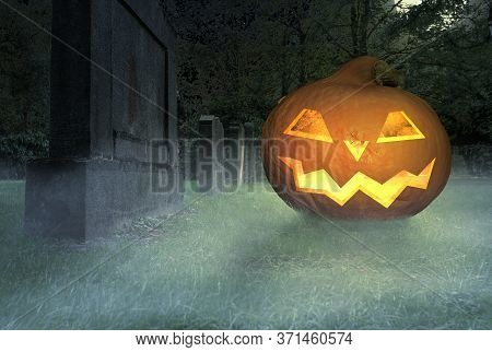A Scary Grinning Halloween Pumpkin Lies On A Cemetery