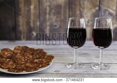 Typical Spanish Chorizo Sausage Sliced On A Plate And Two Red Wine Glasse