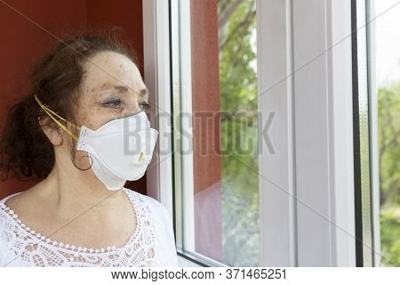 Old Woman Under Quarantine In Her Home, Wearing A Medical Mask, Is Standing In Front Of A Closed Win