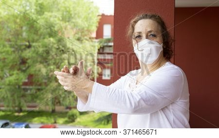 Portrait Of Old Woman Wearing Medical Mask Applauding From The Balcony In Gratitude To The Health Wo