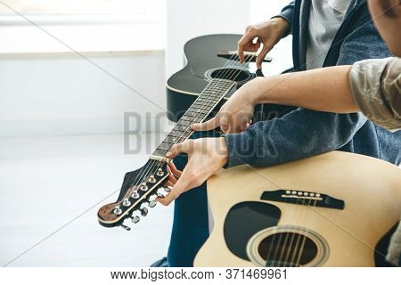 Learning To Play The Guitar. The Teacher Helps The Student Tune The Guitar And Explains The Basics O