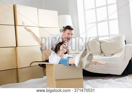 Husband And Wife Have Fun Unpacking Boxes In Their New Apartment