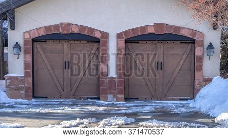 Panorama Facade Of A Residential Garage With Gable Roof And Two Hinged Wooden Doors