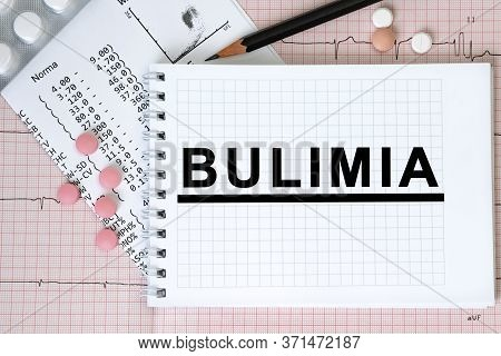Notebook Page With Text Bulimia On A Table With A Pills And Pencil, Medical Concept, Top View