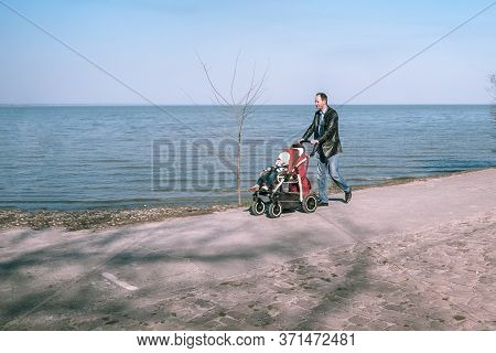 Taganrog, Russia - 07.04.19: A Man Walks Along The Promenade With A Small Child In A Stroller. Fathe