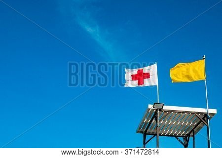 Two Developing Flags Against A Blue Sky. White With A Red Cross Flag On The Tower. A Yellow Flag Nex