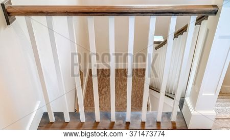 Panorama Crop U Shaped Stairway Of Home With Brwon Handrail Supported By White Balusters