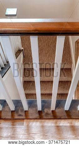 Vertical Frame U Shaped Staircase With White Baluster Brown Handrail And Carpet On Treads