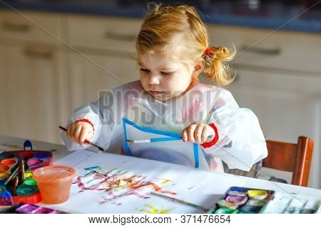 Adorable Baby Girl Learning Painting With Water Colors. Little Toddler Child Drawing At Home, During