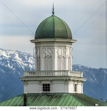 Square Building Exterior With Green Dome And Roof Against Snowy Mountain And Cloudy Sky