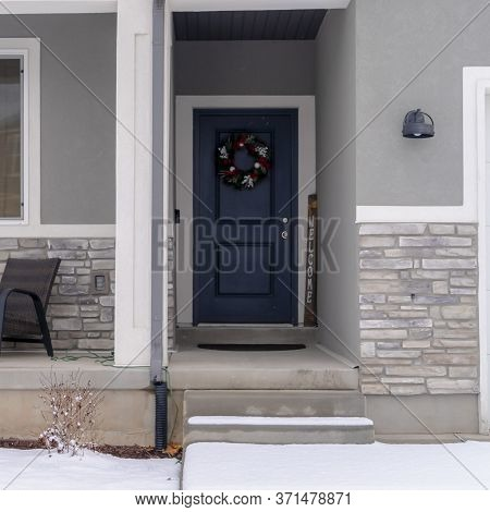 Square Crop Home Facade With Gable Roof Front Porch And Door With Wreath In Winter