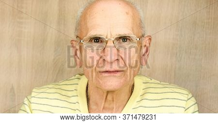 Bald Elderly Man In Glasses And Yellow Striped Pullover Looks Into Camera Against Brown Wooden Wall