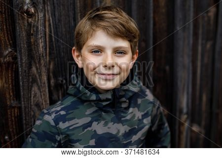 Outdoor Portrait Of Happy Smiling Preteen Kid Boy Wearing Rain Jacket On Rainy Cloudy Day. Handsome