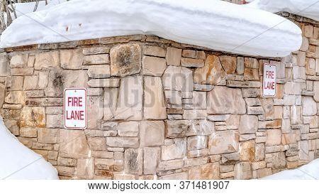 Panorama Stone Retaining Wall With Fire Lane Sign On A Hill With Thick Snow In Winter