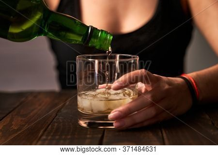 Drunk Woman's Hand Putting On A Glass Of Alcohol. Concept Of Alcoholism And Addictions.