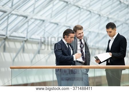 Business People Having Informal Meeting In Modern Office Discussing Documents