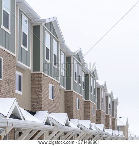 Square Crop Townhome Facade With Snowy Gabled Roof At The Entrance In Winter