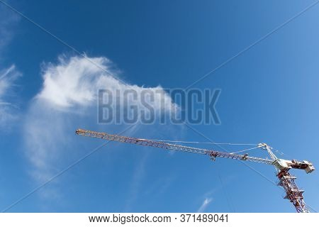 Construction Tower Crane Against The Blue Sky. Concept Of Development Of The Architectural Appearanc