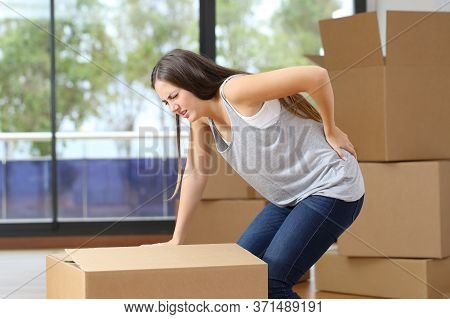 Woman In Pain Moving Boxes Suffering Backache Grabbinng Lumbar Area At Home