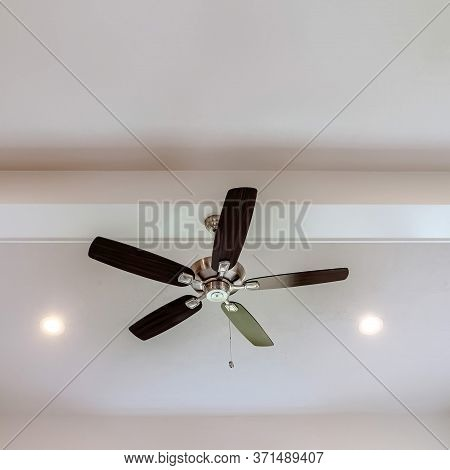 Square Frame Ceiling Fan With Wood Blades And Built In Lights On The Ceiling Beam Of Home
